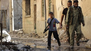A boy carries a weapon as he walks with members of the Free Syrian Army in Deir al-Zor