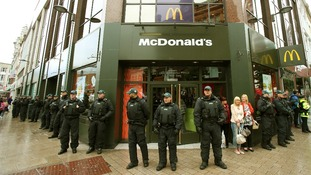 Police in riot gear guard a branch of McDonald's in Belfast, Northern Ireland