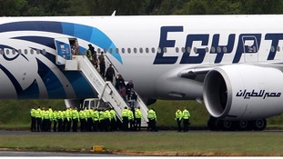Passengers leave the Egyptair aircraft flying from Cairo to New York after it was diverted to Prestwick Airport