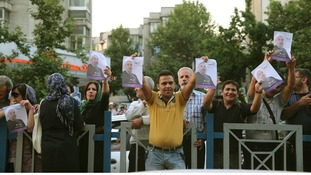 Supporters of Iran's future president, Hassan Rouhani, hold pictures of their man