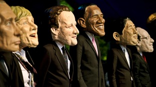 Large headed impersonators of the G8 politicians arrive onstage at Belfast Botanic Gardens