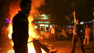 Protesters set fire to a barricade as they clash with riot police in Istanbul.