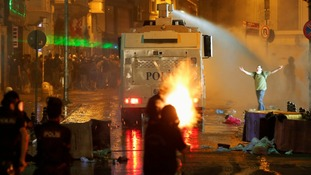 Riot police fire tear gas and a water cannon at Taksim Square in Istanbul.