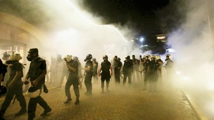 Riot police walk in front of Divan hotel in Istanbul amid a cloud of tear gas.