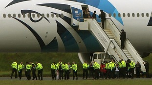 Passengers pictured leaving the Egyptair aircraft yesterday surrounded by police.