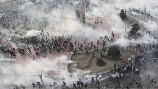 Protesters flee as tear gas fills the square in protests earlier this week.
