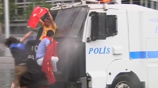 Protesters trying to climb onto a water cannon truck in Istanbul, Turkey