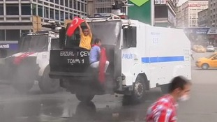 A protester waves a Turkish flag in front of the windscreen