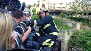 A firefighter speaks to punters trapped on the ride