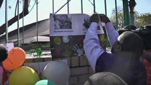 One family member removes a mural to take inside to Nelson Mandela.