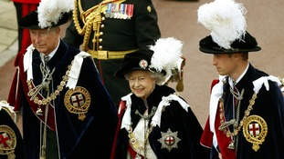 The Queen walks in procession with The Price of Wales and The Duke of Cambridge