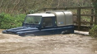 A Landrover is surrounded by water after heavy rainfall