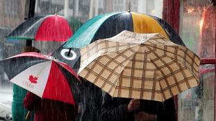 Shoppers use their umbrellas to shield from rain in Straford upon Avon city centre