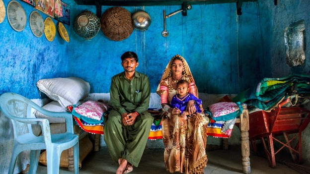 Shugna, holding their daughter Kawila, and Marjee sit in their house in Umerkot District, Sindh province, Pakistan, April 10, 2013.