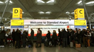 Passengers queue at Stansted Airport