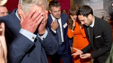 The Prince of Wales grimaces and looks away as illusionist Dynamo performs his trick.