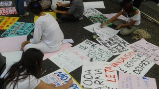 Protesters paint banners for their demonstration
