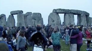 People gather around the stone pillars of Stonehenge