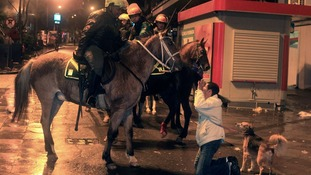 A woman kneels in front of mounted riot policemen amid anti-government protest in Porto Alegre, southern Brazil