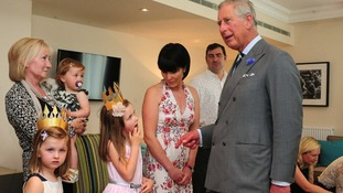 The Prince of Wales meets birthday girl Mia Gammel, six, with her mother Kelly, during his visit to Fisher House UK.