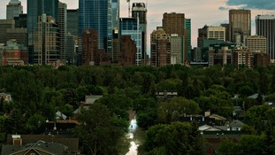 A man walks down a flooded street in the city of Calgary