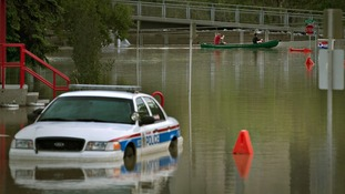 Residents pass a submerged police car by canoe in the city of Calgary