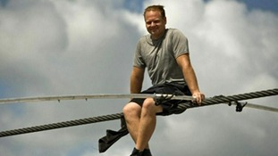 Nik Wallenda sits on the wire he will use to cross Grand Canyon