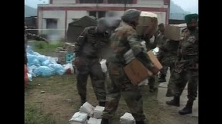 Members of the Indian armed forces help carry supplies to flood victims