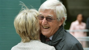 Sir Michael Parkinson is greeted by Michael Winners' widow Geraldine Winner.