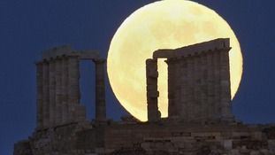 Supermoon rises over the temple of Poseidon, the ancient Greek god of the seas, in Cape Sounion