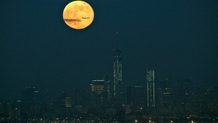 The full moon rises above the New York City skyline