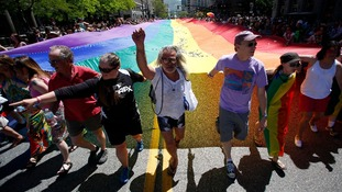 Gay rights supporters march with a rainbow flag during the gay pride parade in Salt Lake City earlier this month.