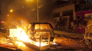 Riot police on horseback pass a burning car near the Mineirao Stadium