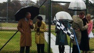 The Prince of Wales and the Duchess of Cornwall under umbrellas in Douglas