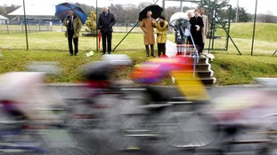 Cyclists fly past the Duke and Duchess of Cornwall during a race