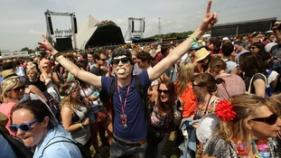 A man in Sir Mick Jagger mask dances among the Glastonbury crowd.