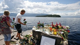 Tributes paid to the dead in Norway with Utoeya island in the background, where the majority of the killings took place.