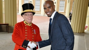Mo Farah shakes hands with Alan Jenkins as he arrives for investiture ceremony.