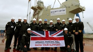 Navy personnel with an Armed Forces Day Flag