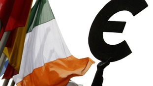 An Irish flag flies next to a symbol of the euro currency at the entrance of the European Parliament in Brussels.