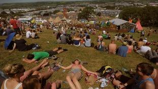 Festival goers enjoy the sunshine at the Glastonbury Festival, at Worthy Farm in Somerset