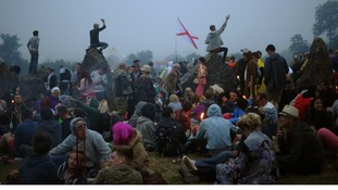 Festival-goers gather in the stone circle at dawn on the final day of the festival