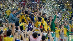 Brazil's players celebrate on the podium with the trophy