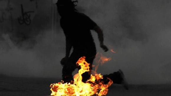 A Bahraini anti-government protester runs from tear gas fired by riot police.