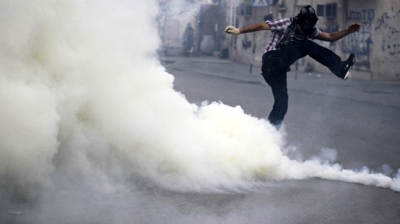 A Bahraini anti-government protester kicks away a tear gas canister fired by riot police.