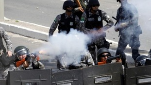 Riot police fire tear gas at protesters near the Estadio Castelao in Fortaleza, Ceará