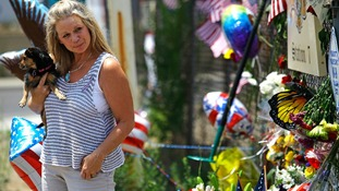 A woman carries her dog as she views a makeshift memorial in Prescott, Arizona