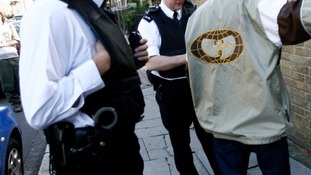 Police stop and search a man in Brixton, south London.
