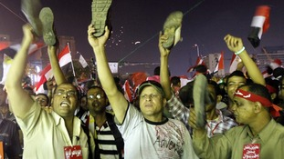 Anti-President Mursi protesters hold up their shoes after his defiant speech yesterday in Tahrir Square.