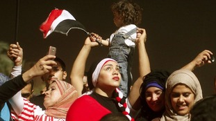 An anti-Morsi protester holds a young child above the crowd